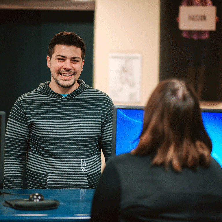 Student standing at the Bepko Learning Center helpdesk.